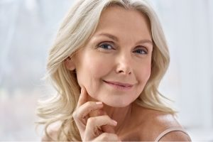 Smiling, happy, attractive mature blond woman, looking at camera advertising anti age face skin and body care treatment cosmetics